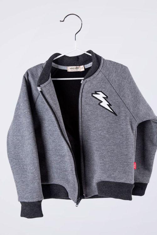 chamarra gris con puños y cuello en negro y bordado de rayo al frente
